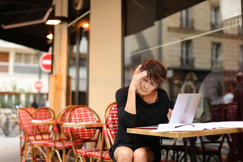 Aged female writer working with new book in laptop and have. R aged female writer printing in laptop have some difficulties with writing new part of novel. Woman royalty free stock photos