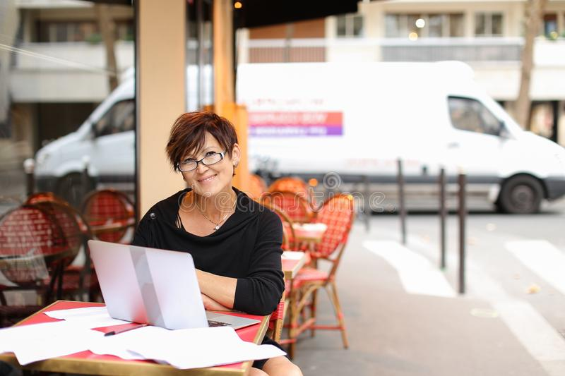 aged female writer working with new book in laptop and have stock images