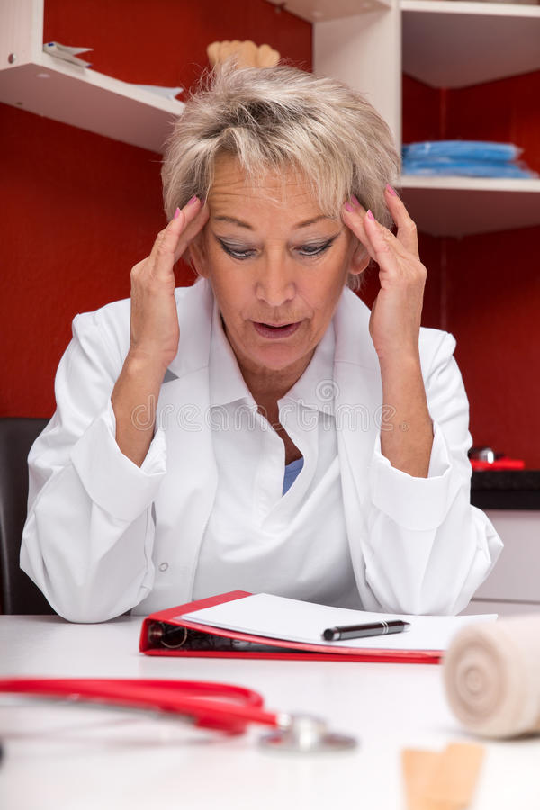 Aged femlae doctor with headache. Maybe burnout, documents on a table, red office royalty free stock photography
