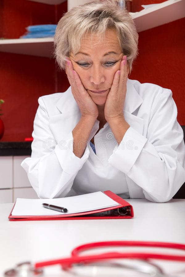 Aged female doctor, in front a plastic brain. Aged femlae doctor is stressed, maybe burnout, documents on a table, red office stock photography
