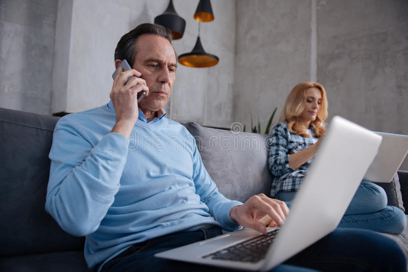 Aged freelancer working with wife at home. Career first of all in my life. Serious aging involved men sitting at home and using modern gadgets with wife while stock photos