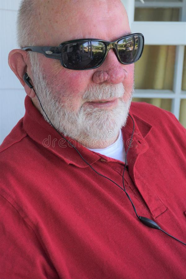 Aged gentleman listens through earbuds. Elderly man with white beard, black sunglasses, red shirt sits enthralled at what he hears. Soft inserts take the place royalty free stock photos