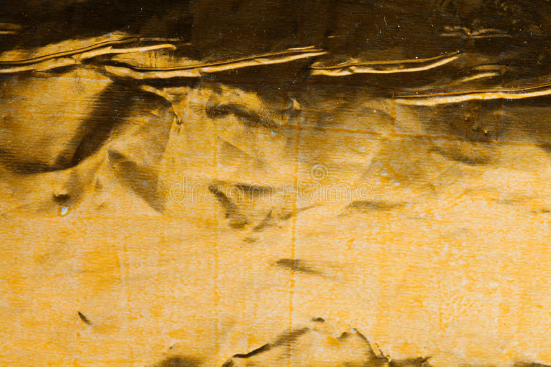 Aged golden metal foil with a coloring traces. Orange yellow colorful crumpled paper shabby and dust. Decorative stock photo