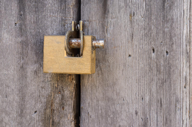 Aged grunge gold lock pad on vintage ancient wooden door royalty free stock images
