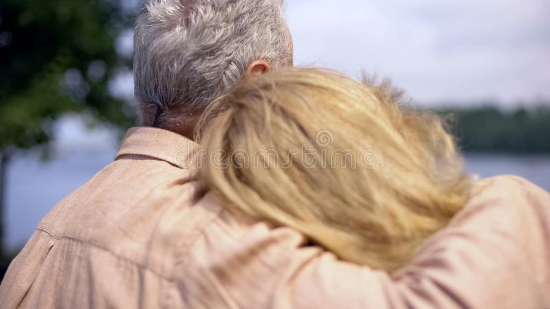 Aged husband hugging wife, happy couple sitting on park bench together, peace stock photos