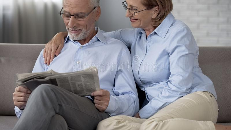 Aged husband reading newspaper, wife hugging him with love, harmonious couple stock photo