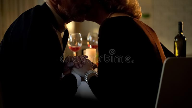 Aged husband and wife kissing and holding hands, celebrating birthday in cafe stock image