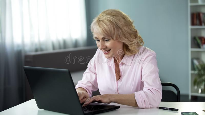 Aged lady actively flirting and chatting with man dating website, typing message. Stock photo royalty free stock photos