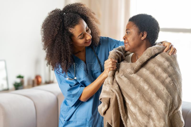 Aged lady feeling thankful to caring nurse in the nursing house. Feeling thankful. Aged sick lady feeling thankful to caring pleasant nurse in the nursing house royalty free stock images