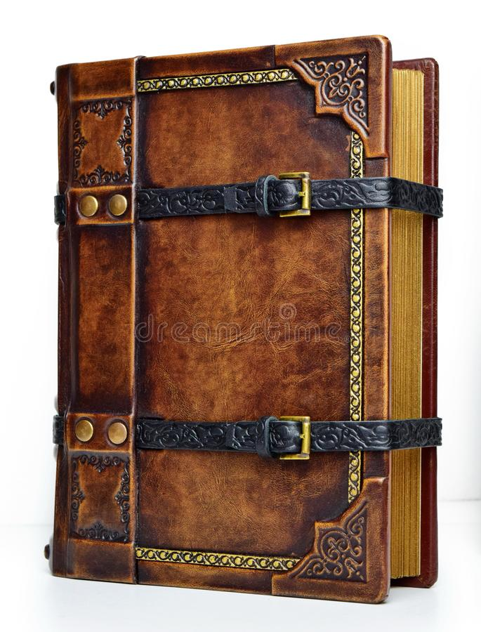 Aged leather book with straps and gilded paper edges - view from the right side. Aged leather book with embossed black straps and gilded paper edges - view from royalty free stock image