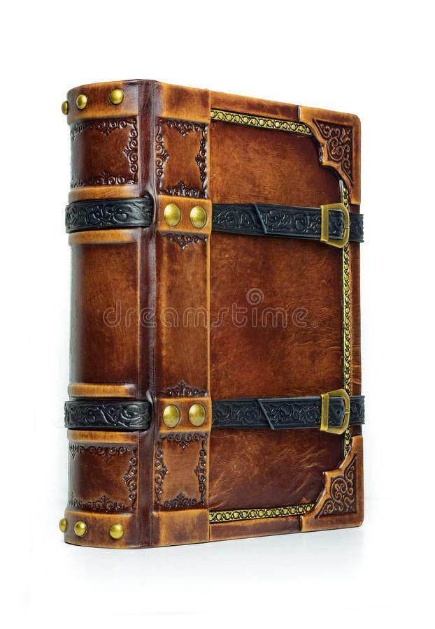 Aged leather book with straps and gilded paper edges. View from the left side royalty free stock photo