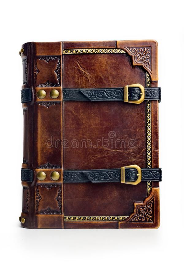 Aged leather book with straps and gilded paper edges. Captured frontal stock photos