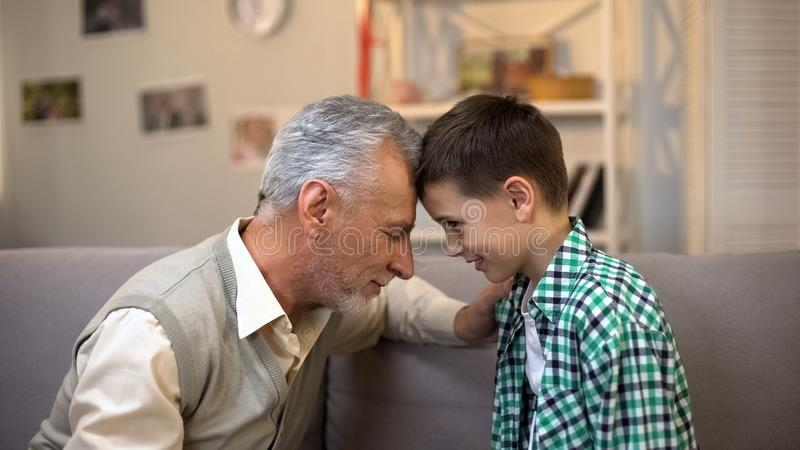 Aged male and boy touching foreheads, friendship between grandpa and grandson royalty free stock photos
