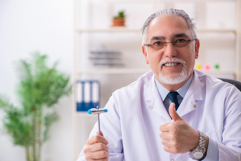 The aged male doctor with hammer. Aged male doctor with hammer stock photography
