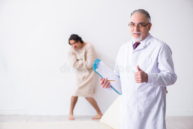 Aged male doctor psychiatrist examining young patient. The aged male doctor psychiatrist examining young patient stock photography