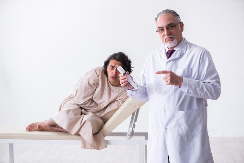Aged male doctor psychiatrist examining young patient. The aged male doctor psychiatrist examining young patient royalty free stock photos