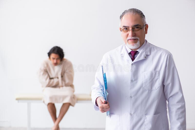 Aged male doctor psychiatrist examining young patient. The aged male doctor psychiatrist examining young patient royalty free stock image