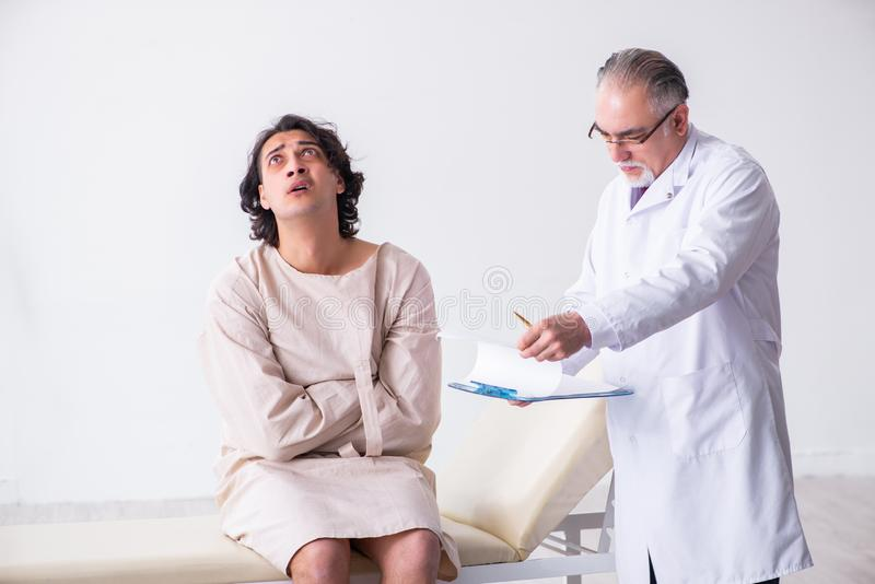Aged male doctor psychiatrist examining young patient. The aged male doctor psychiatrist examining young patient royalty free stock images