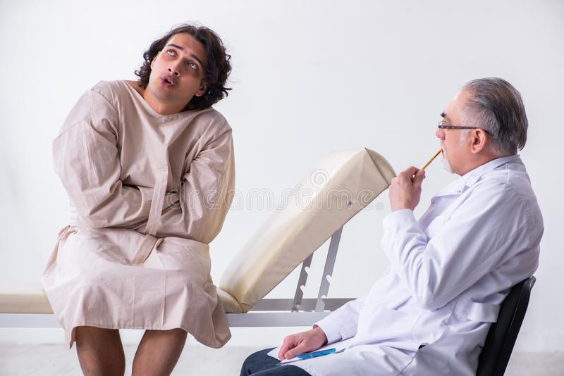 Aged male doctor psychiatrist examining young patient. The aged male doctor psychiatrist examining young patient stock photo