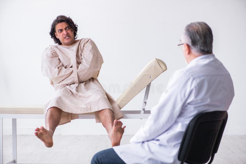 Aged male doctor psychiatrist examining young patient. The aged male doctor psychiatrist examining young patient royalty free stock photography