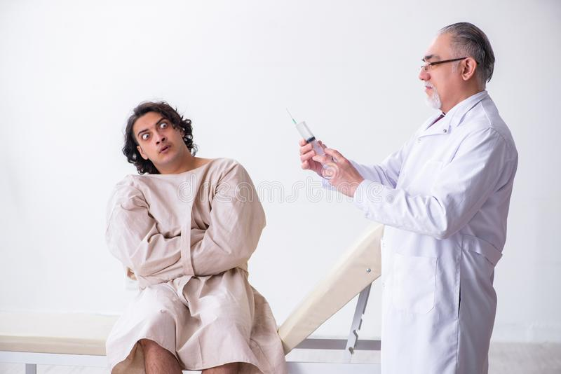 Aged male doctor psychiatrist examining young patient stock photos