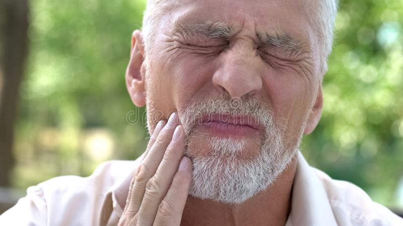 Aged male feeling terrible toothache, dental illness, lack of calcium, caries. Stock photo royalty free stock photography