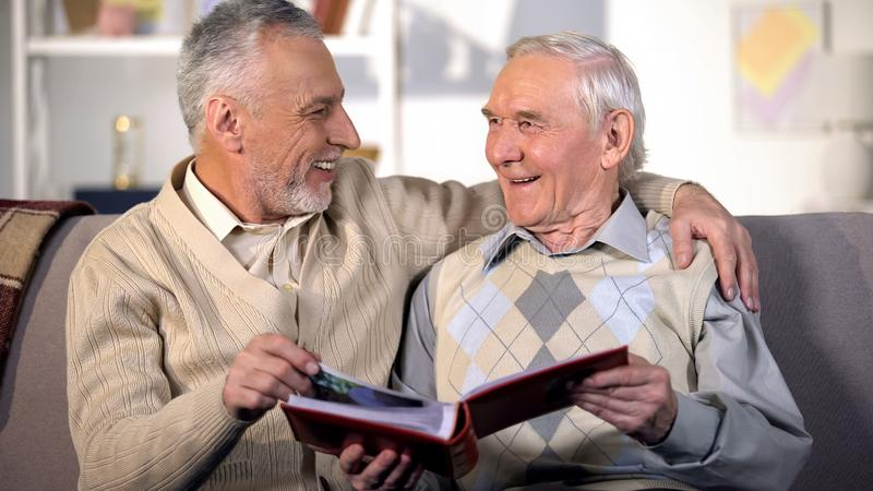 Aged male friends having fun watching album photos together, friendship joy stock image