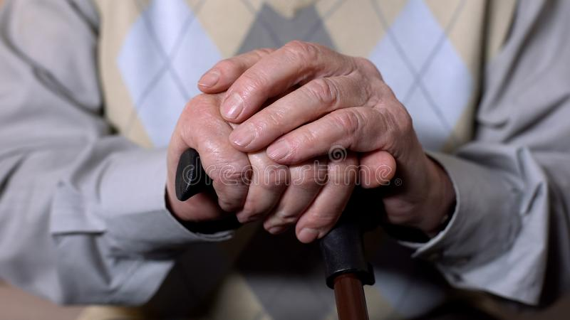 Aged male hands holding walking stick, social pension reform, health care stock photography