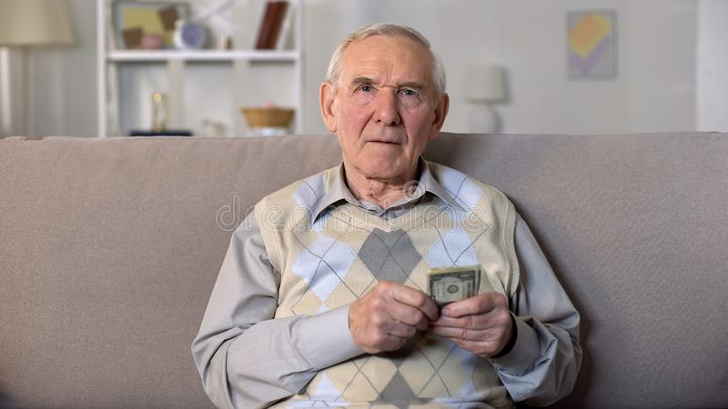 Aged male holding dollars sitting on sofa looking camera, low living standard stock photography