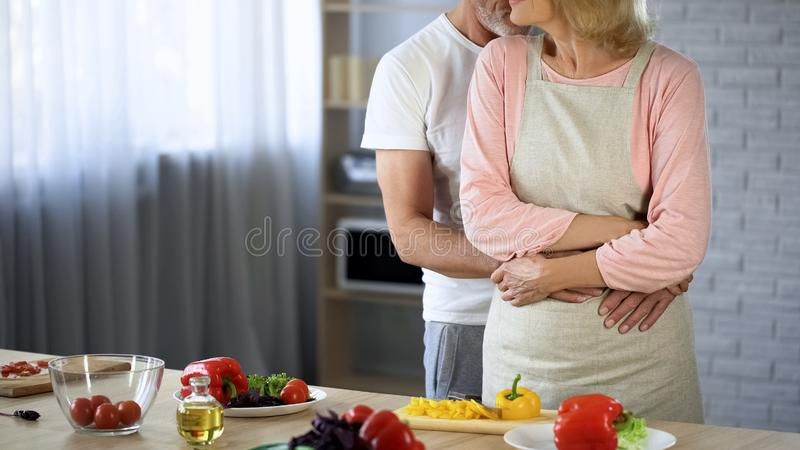 Aged male hugging wife in apron, happily married grandparents, cooking chores royalty free stock images