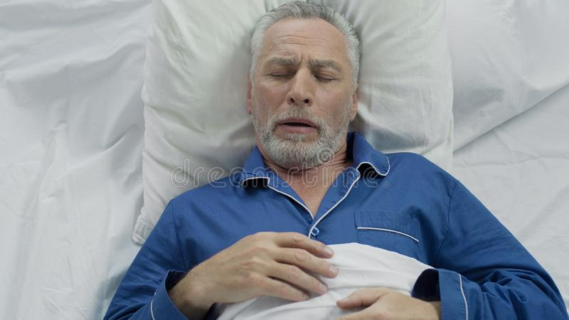 Aged male loudly snoring and puffing in bed, sleeping problems at old age stock images