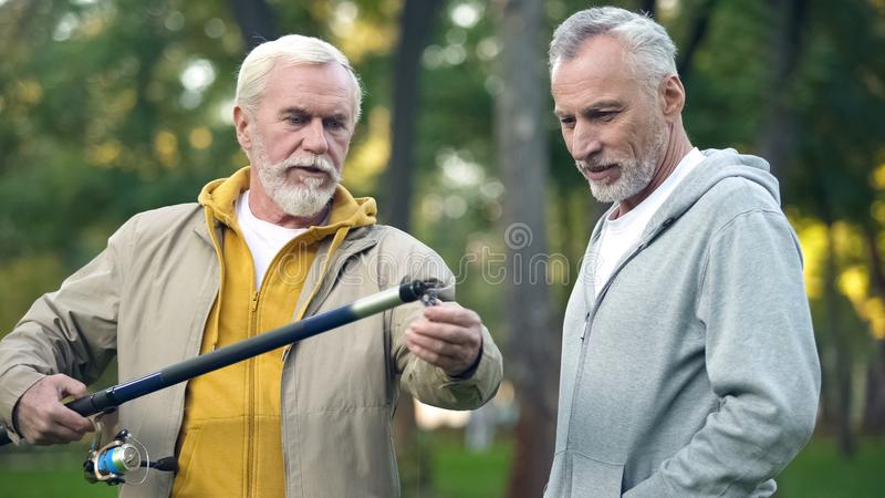 Aged male showing new fishing rod to friend, pensioner hobby, togetherness stock photos