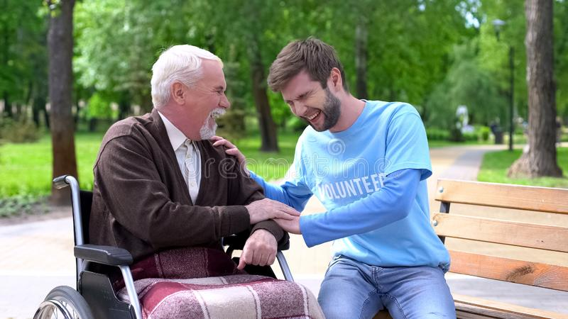 Aged male in wheelchair and volunteer laughing and joking, having fun together stock image