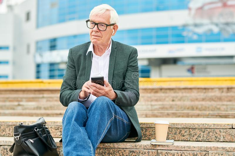 Senior businessman using smartphone and listening to music on steps stock photo