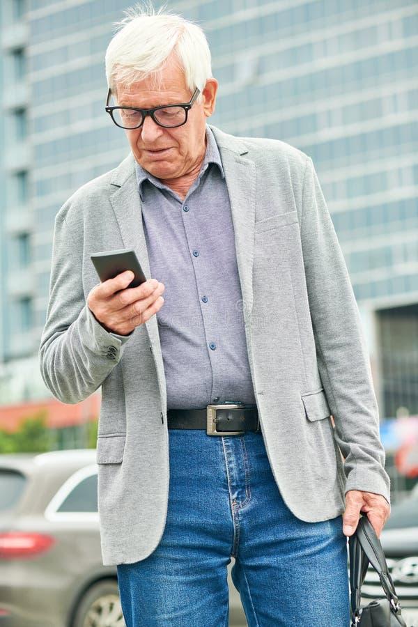 Elderly businessman using smartphone on street royalty free stock image