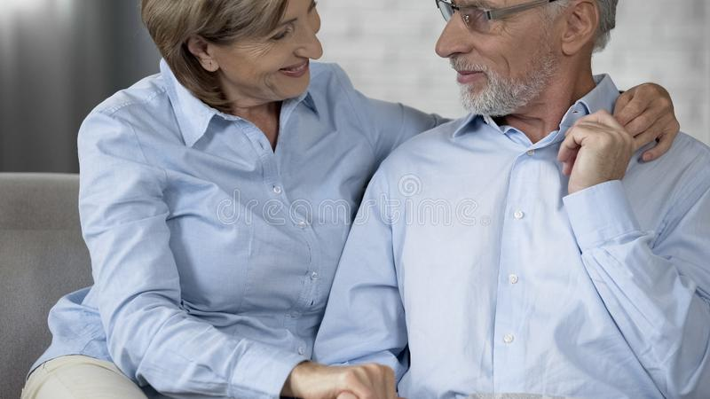Aged man and lady sitting on sofa and looking at each other, happy family moment royalty free stock photos