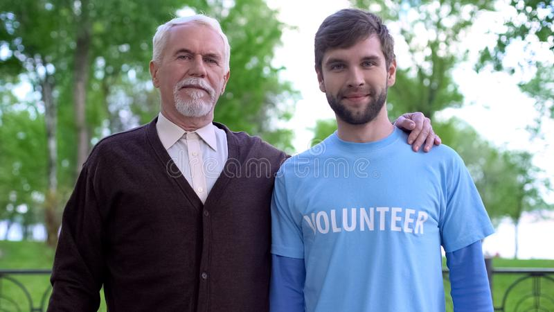 Aged man and male volunteer looking at camera, old people assistance, charity royalty free stock image