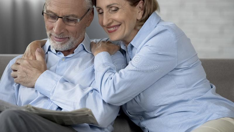 Aged man reading newspaper on couch, wife sitting beside hugging him and smiling royalty free stock image