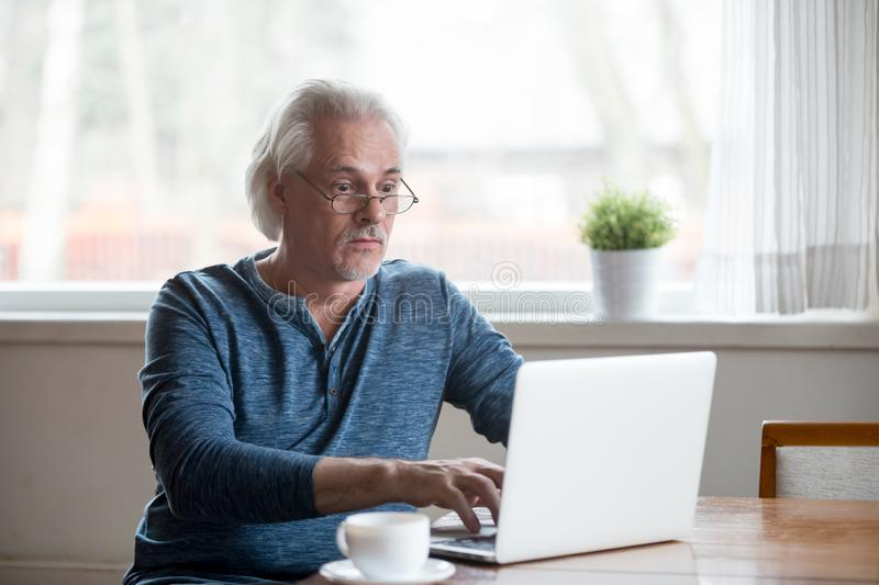 Aged man shocked getting unexpected message on laptop. Surprised aged man stunned getting error or mistake message working at laptop, senior male using pc royalty free stock photo