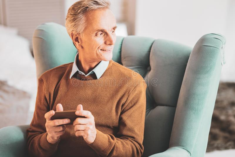 Aged man sitting in leather turquoise armchair at home stock images