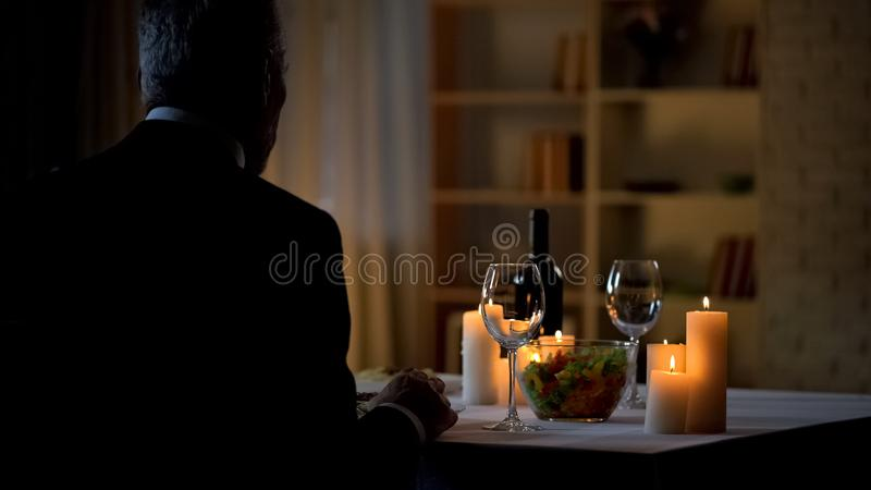 Aged man sitting at table served for romantic dinner, waiting woman, home date royalty free stock photo