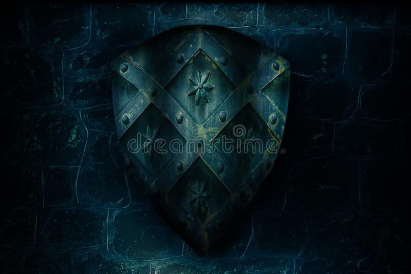 Aged medieval shield. Over castle stone wall royalty free stock photo