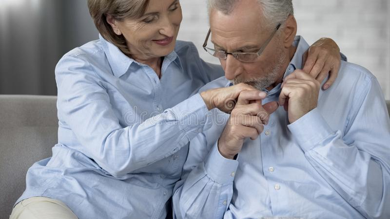 Aged man kissing woman hand, couple sitting on sofa together, loving relations royalty free stock photography