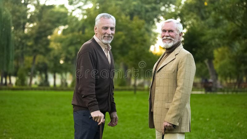 Aged men with walking sticks resting and smiling for camera, male friendship stock photos