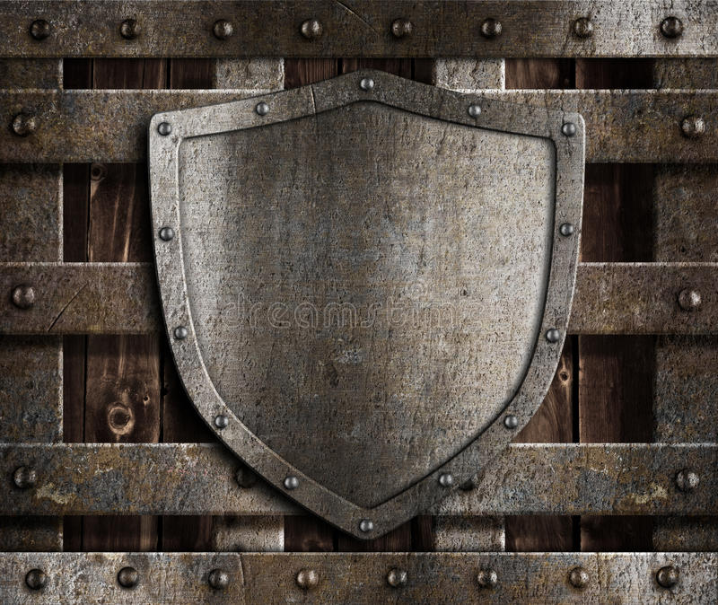 Aged metal shield on wooden medieval gates. Aged metal shield on wooden medieval city gates or wall stock photo