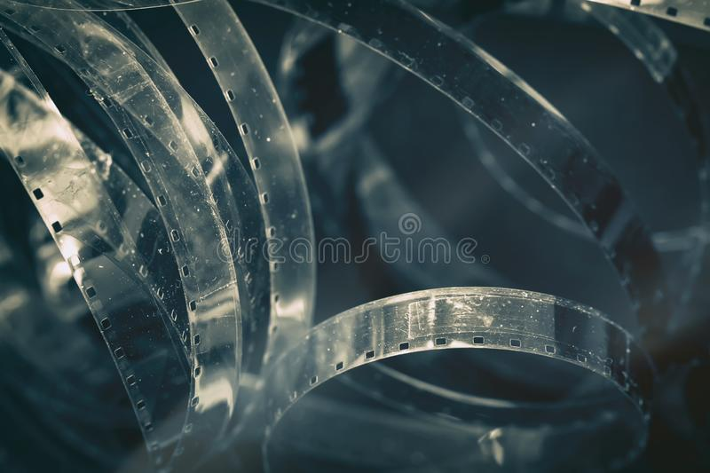 Aged old cinema rolls, retro reels, filmstrip, photographic film with hard grain, dust and scratches. Vintage dark stock photo