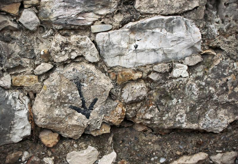 Aged old textured surface stone wall with painted arrow pointing down sign royalty free stock photo