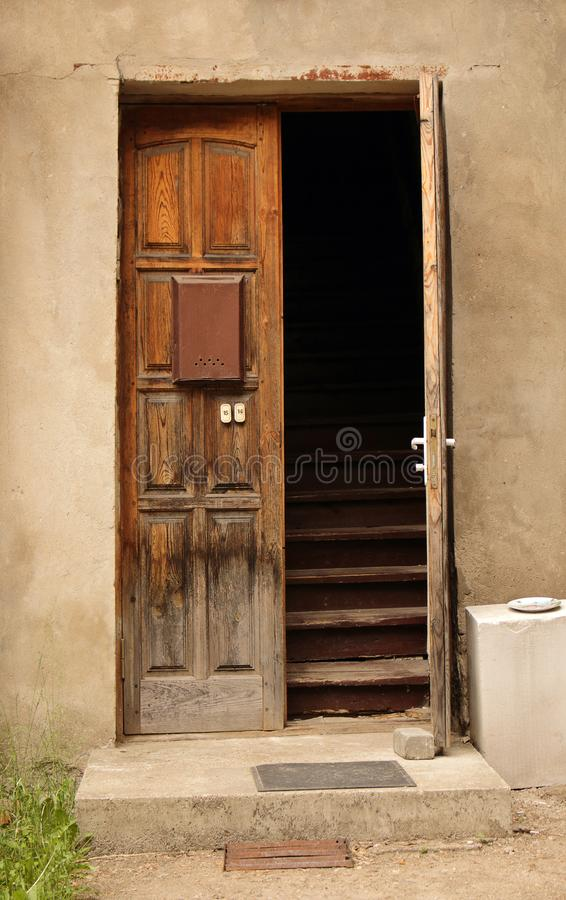 Aged dark wooden door in weathered concrete wall. Aged opened dark wooden door with mail box and stairs royalty free stock images