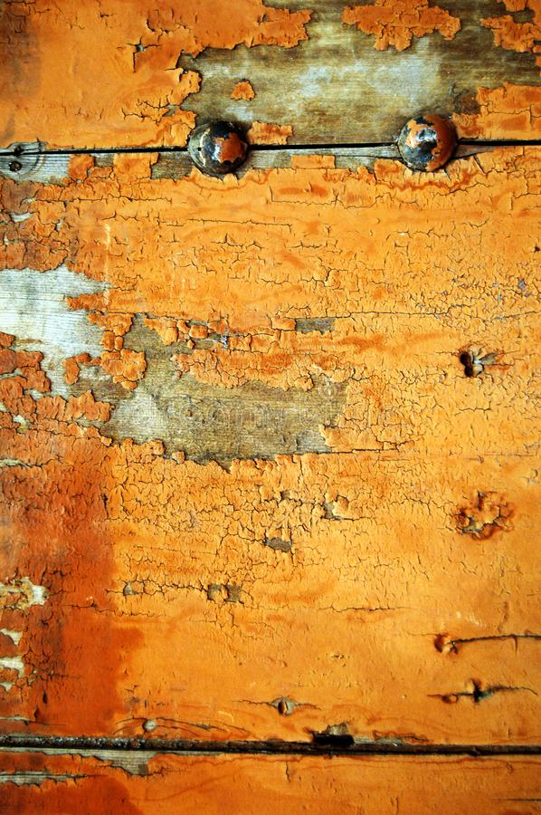 Aged Orange Wood with Rivets. Detail of old wooden door with peeling orange paint and iron bolts royalty free stock image