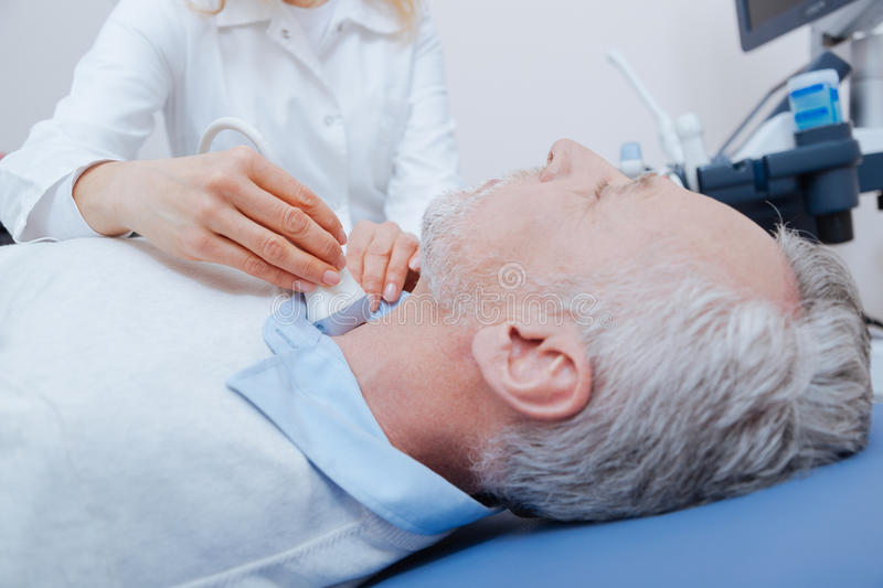 Aged patient getting ultrasound of thyroid in the clinic. Prevention checkup of thyroid gland. Senior motionless bearded patient lying on the medical couch and stock photo